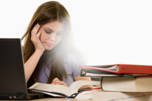 молодая девушка сидит перед компьютером и читает книгу