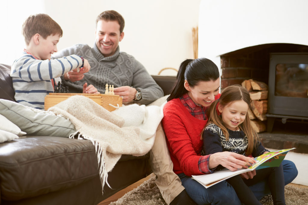 Family Relaxing Indoors Playing Chess And Reading Book Smiling